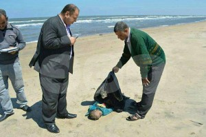 Egyptian officials examine body washed up on beach